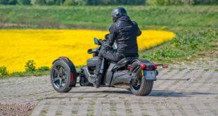 Moto 3 roues dans un champs de fleurs jaunes.